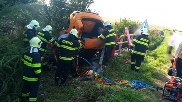 Hasiči vyprošťovali řidiče, který s osobním vozem narazil do mostku a skončil převrácený přes mostek ve vzpříčené poloze