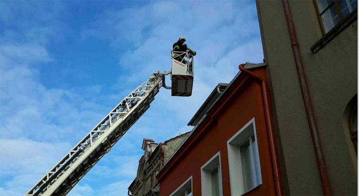 Uvolněná atika na historické zdi hrozila pádem, sundat ji museli hasiči